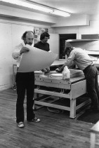 Richard Hamilton examining a newly printed lithography impression, Kenneth Tyler inking and Robert Bigelow sponging one of the artist's 'Flower Piece' series stones on the press-bed, Tyler Graphics Ltd., Bedford Village, New York, 1976