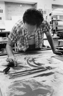 Ed Baynard using his finger to ink a passage on the third woodblock during the trial proofing of his 'The Dragonfly Vase' print on the lithography offset press bed, Tyler Graphics Ltd. workshop, Bedford Village, New York, 1980. Photo: Lindsay Green
