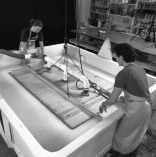 Jed Marshall (left) and Tom Strianese lowering the Frank Stella 'Moby Dick Domes' shaped papermaking vacuum mould into the vat of paper pulp, while vacuum suction pulls the pulp slurry against the submerged mould, Tyler Graphics paper mill, Mount Kisco, New York, 1991. Photo: Steven Sloman