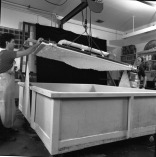 Tom Strianese and Jed Marshall lift newly formed sheet of paper pulp on shaped papermaking vacuum mould from paper pulp vat, Tyler Graphics paper mill, Mount Kisco, New York, 1991. Photo: Steven Sloman