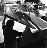 The shaped vacuum papermaking mould is attached to a pivot and disconnected from the electric hoist and vacuum tube so that it can be rotated face-upwards, Tyler Graphics paper mill, Mount Kisco, New York, 1991. Photo: Steven Sloman