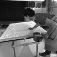 While newly vacuum formed paper pulp sheet is draining excess water over paper pulp vat, Tom Strianese adds pulp along the perimeter of the dome-shaped section, flattening the edges and strengthening the paper pulp structure for one of Frank Stella's 'Moby Dick Domes' series papers, Tyler Graphics paper mill, Mount Kisco, New York, 1991. Photo: Steven Sloman