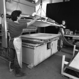 Tom Strianese (left) and Jed Marshall lower newly formed paper pulp dome adhered onto shaped vacuum mould into felt-lined 'female' half of mould on hydraulic platen press bed, for Frank Stella's 'Moby Dick Domes' series paper to be pressed, Tyler Graphics paper mill, Mount Kisco, New York, 1991. Photo: Steven Sloman
