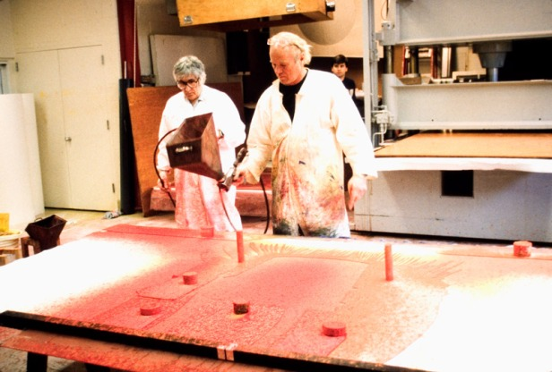 James Rosenquist assisted by Kenneth Tyler using a pattern pistol to spray red coloured paper pulp through plastic stencil on newly made paper pulp sheet in paper mill with hydraulic platen press in background, Tyler Graphics Ltd., Mount Kisco, New York, 1989. Photographer: Marabeth Cohen-Tyler