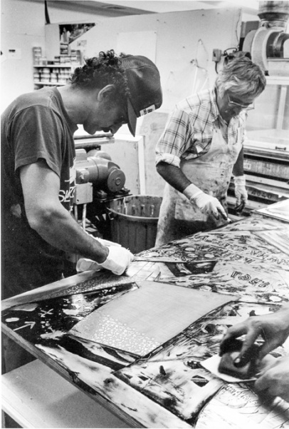 Frank Stella and Kenneth Tyler inking relief sections of a 'Swan engraving' plate and wiping the plate with scraps of newsprint, Tyler Graphics Ltd., Bedford Village, New York, 1981